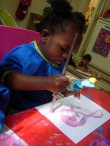 Child painting in the Busy Bees room at Early Learners' Nursery School, Leicester