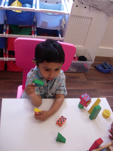 Child playing with blocks in the Busy Bees room at Early Learners' Nursery School, Leicester