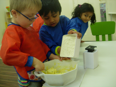 Pre-school children learning to cook at Early Learners' Nursery School, Leicester